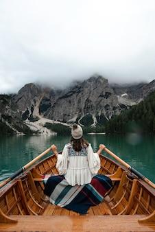 Szczęśliwa turystka kobieta z kapeluszem siedzi w drewnianej łodzi na jeziorze braies otoczonym górami włoskich alp