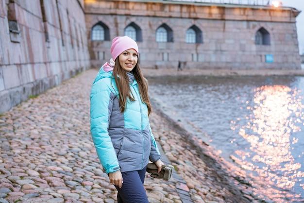 Szczęśliwa turystka na brzegu rzeki jesienią w ciepłych ubraniach turyści cieszą się wakacjami...