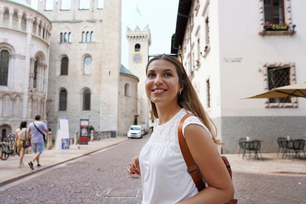 Szczęśliwa turystka odwiedzająca stare średniowieczne miasto trento, włochy