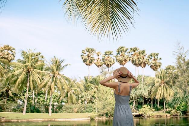 Szczęśliwa turystka w sukience i słomkowym kapeluszu rozkłada ręce na bok