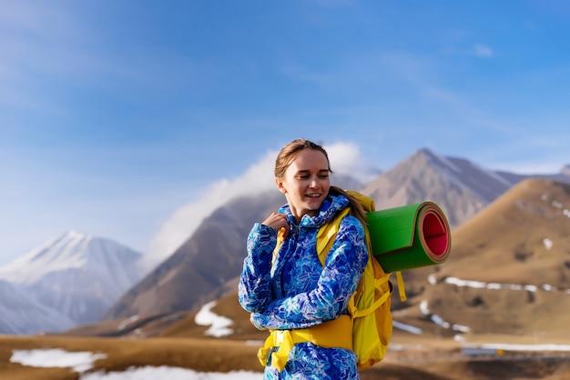 Szczęśliwa turystka z dużym plecakiem na tle wysokich gór