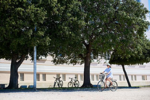 Szczęśliwa turystyczna kobieta jedzie bicykl wzdłuż plecaka brukującą pogodną ulicę na jaskrawym słonecznym dniu z plecakiem. zabytkowy budynek, parking dla rowerów i zielone drzewa