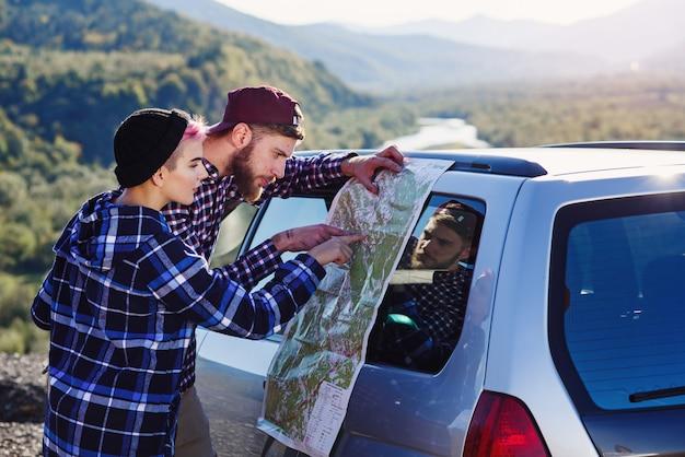 Szczęśliwa turystyczna para z papierową mapą blisko samochodu.
