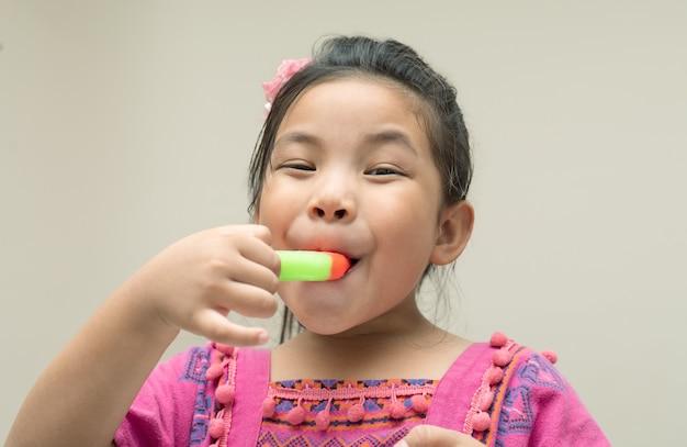 Szczęśliwa twarz dziewczyna do jedzenia lodów, bliska strzał z miejsca na kopię.