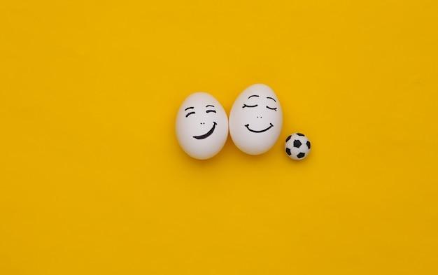 Szczęśliwa twarz jajka z piłką nożną na żółtym tle
