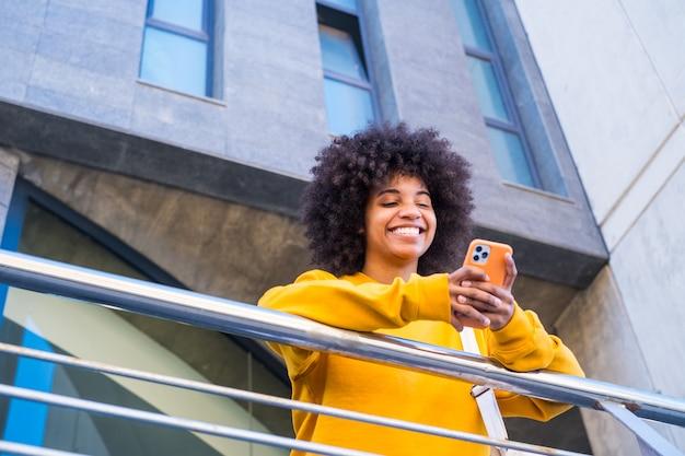 Szczęśliwa tysiącletnia dziewczyna rasy mieszanej na ulicy miasta. pozytywna młoda afroamerykanka surfowanie po sieci, wyszukiwanie informacji, zakupy w sklepie internetowym na świeżym powietrzu