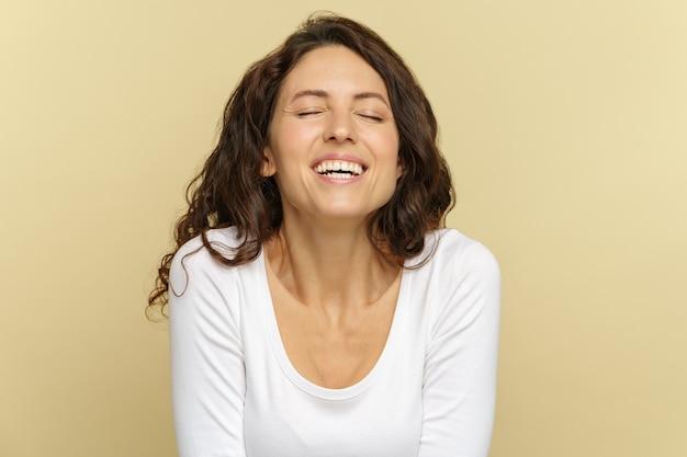 Szczęśliwa tysiącletnia kobieta z zamkniętymi oczami uśmiecha się do kamery nad beżową ścianą portret śmiejącej się kobiety