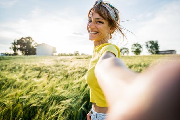 Szczęśliwa tysiącletnia piękna kobieta bierze selfie portret z smartphone na pszenicznym polu przy latem. portret uśmiechniętej dziewczyny patrzeć