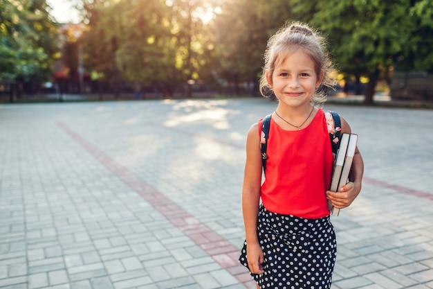 Szczęśliwa uczeń dziewczyna jest ubranym plecaka i trzyma książki