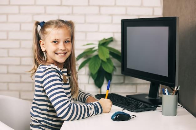 Szczęśliwa uczennica dziewczyna odrabiania lekcji, siedząc przy stole