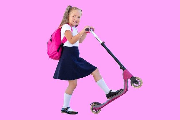 Szczęśliwa uczennica na hulajnodze z plecakiem. izolować na różowym tle