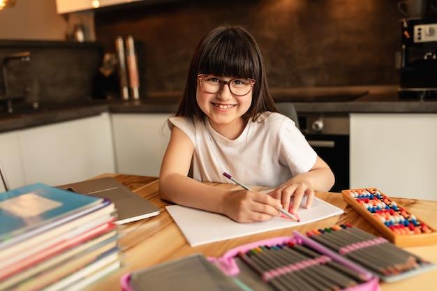 Szczęśliwa uczennica odrabia lekcje w domu. uczenie się online bez cyfrowych gadżetów. kształcenie na odległość, nauczanie w domu
