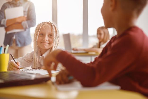 Szczęśliwa uczennica patrząca na koleżankę z klasy na lekcji