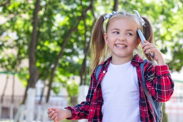 Szczęśliwa uczennica rozmawia przez telefon z plecakiem