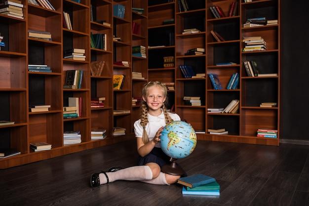 Szczęśliwa uczennica w mundurku szkolnym siedzi z kulą ziemską i książkami w bibliotece