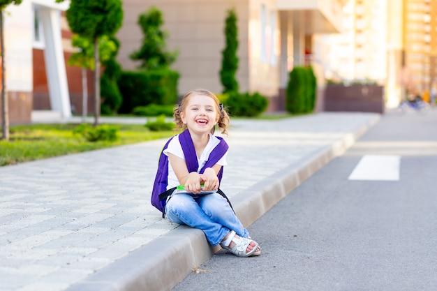 Szczęśliwa uczennica z plecakiem i podręcznikami w rękach siedzi na krawężniku w szkole, koncepcja wraca do szkoły