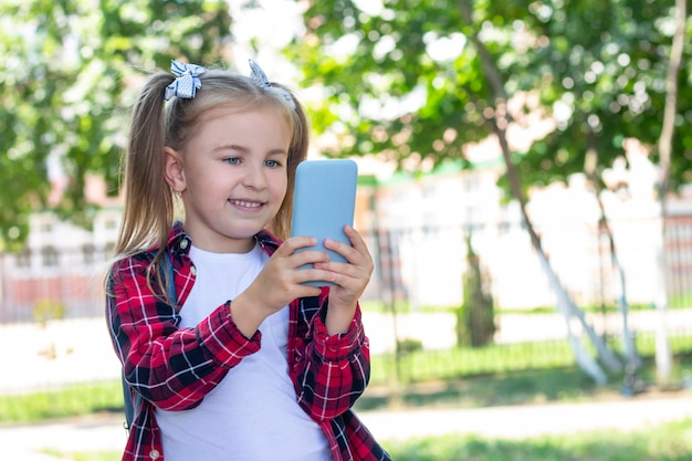 Szczęśliwa uczennica z plecakiem rozmawia przez telefon na ulicy