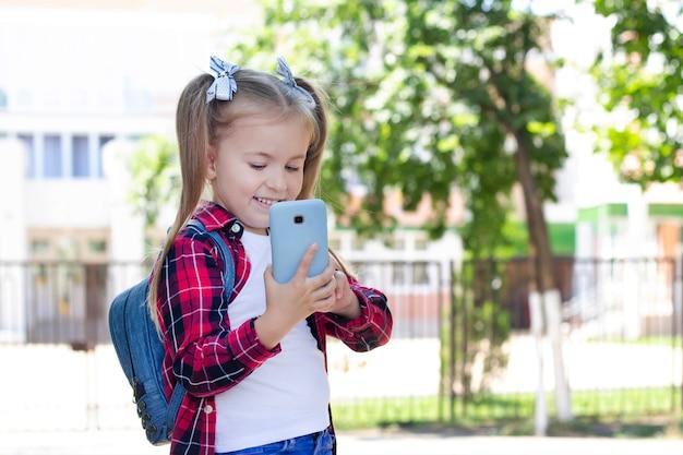 Szczęśliwa uczennica z plecakiem rozmawia przez telefon na ulicy.