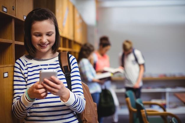 Szczęśliwa uczennica za pomocą telefonu komórkowego w szatni