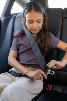 Szczęśliwa uczennica zapinająca pasy w samochodzie