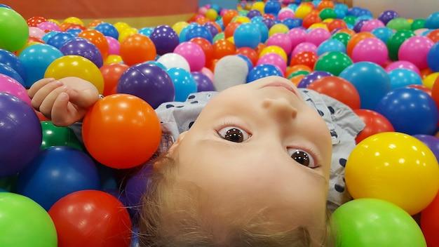 Szczęśliwa urocza dziewczyna bawi się w basenie z piłeczkami w parku rozrywki dla dzieci i centrum zabaw dla dzieci