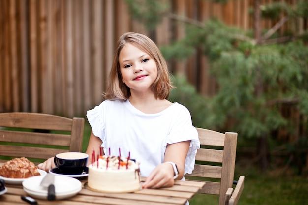 Szczęśliwa urocza dziewczyna jedzenie tort urodzinowy na tarasie kawiarni. 10-latek świętuje urodziny.