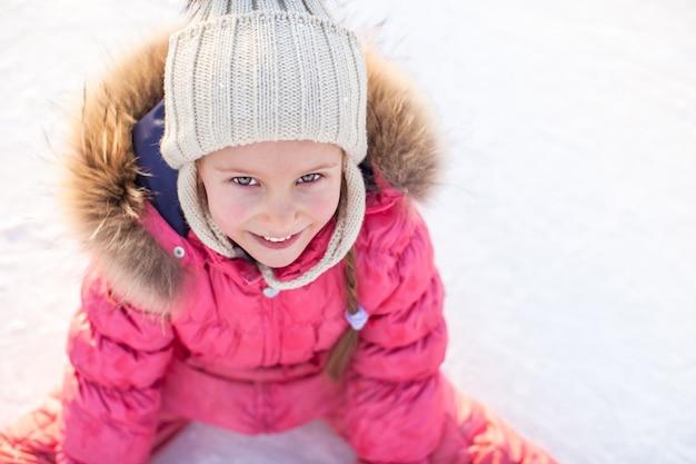 Szczęśliwa urocza dziewczyna siedzi na lodzie z łyżwy po upadku