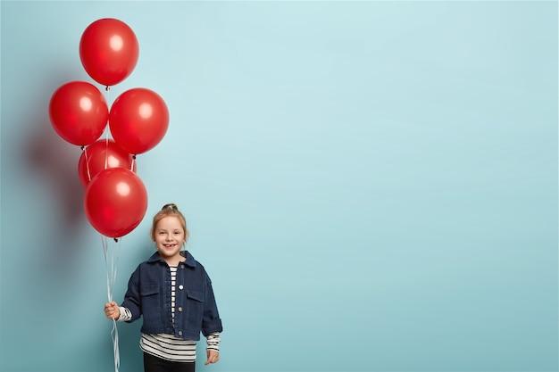 Szczęśliwa urocza dziewczyna z balonami, ma zabawny wygląd, ubrana w dżinsowe ubrania, stoi nad niebieską ścianą z wolną przestrzenią po prawej stronie na twoje materiały promocyjne. dziecko bawi się na imprezie
