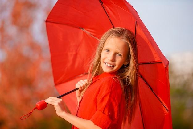 Szczęśliwa urocza dziewczyna z czerwonym parasolem na jesieni