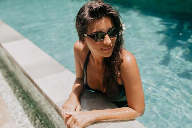 Szczęśliwa urocza europejska dama o długich ciemnych włosach odpoczywa w ośrodku i pływa w basenie w słoneczny, ciepły dzień
