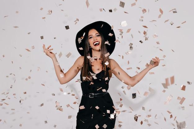 Szczęśliwa urocza jasna modelka w czarnym kostiumie halloween czarownicy na imprezie nad białą ścianą z confeti