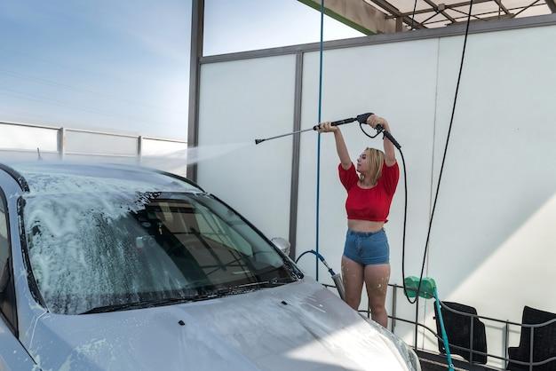 Szczęśliwa urocza kobieta czyści swój samochód pistoletem na wodę pod wysokim ciśnieniem. ręczne mycie automatyczne