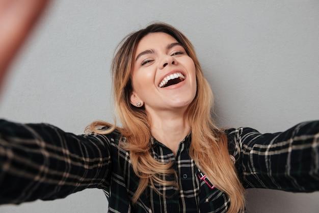Szczęśliwa urocza kobieta robi selfie z telefonem komórkowym
