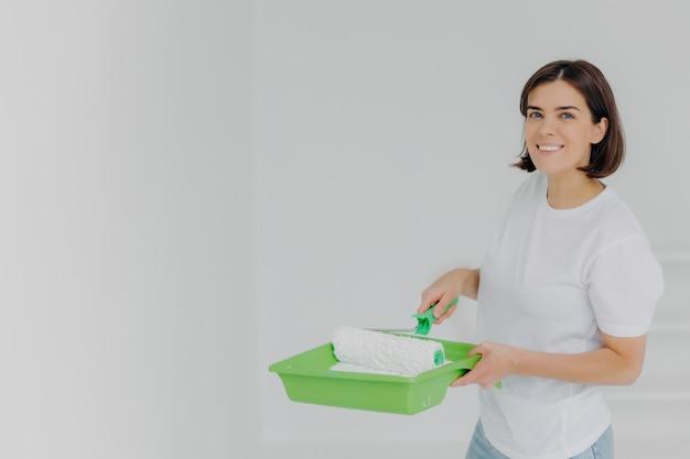Szczęśliwa urocza kobieta w białej koszulce na co dzień, pozach z wałkiem do malowania i specjalnej tacy