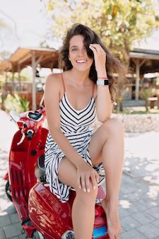 Szczęśliwa urocza ładna dama o kręconych ciemnych włosach nosi letnią sukienkę siedzącą na czerwonym motocyklu przy egzotycznych zielonych roślinach