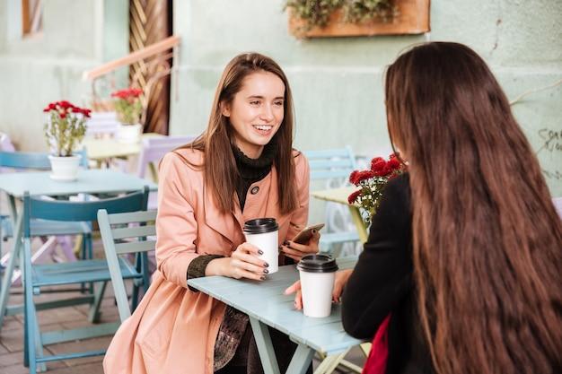 Szczęśliwa urocza młoda kobieta pije kawę i rozmawia ze swoim przyjacielem w kawiarni na świeżym powietrzu