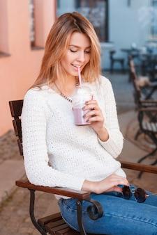 Szczęśliwa urocza młoda kobieta w modnych letnich ubraniach siedzi w kawiarni ulicznej vintage i popija słodki koktajl. wesoła, radosna, stylowa dziewczyna.