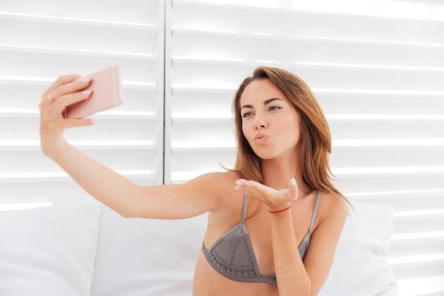 Szczęśliwa urocza młoda kobieta wysyła buziaka i robi selfie za pomocą smartfona