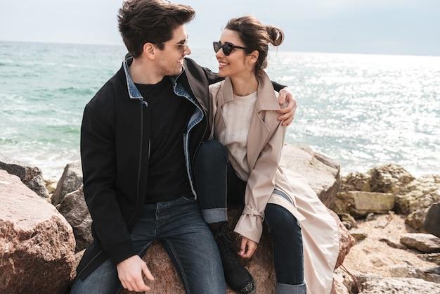 Szczęśliwa urocza młoda para w płaszczach siedzi na plaży, trzymając się za ręce, obejmując