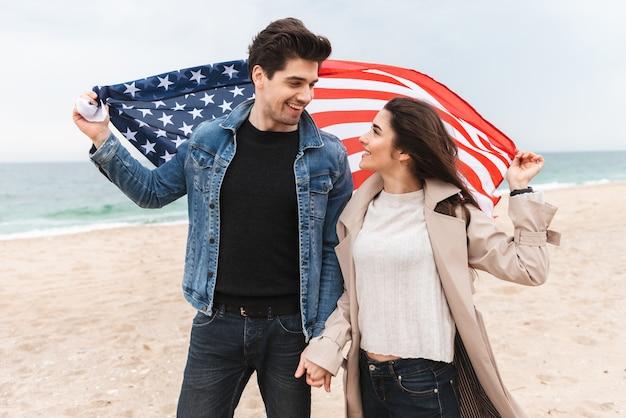 Szczęśliwa urocza młoda para w płaszczach spacerująca po plaży, trzymająca się za ręce, niosąca amerykańską flagę