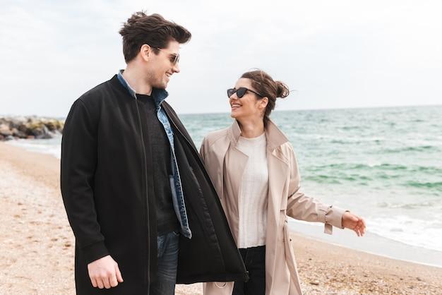 Szczęśliwa urocza młoda para w płaszczach spacerująca po plaży, trzymająca się za ręce