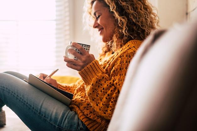 Szczęśliwa urocza pani w domu pisze notatki w pamiętniku, pijąc filiżankę herbaty i odpoczywając i relaksując się, robiąc sobie przerwę