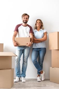 Szczęśliwa urocza para przeprowadza się do nowego mieszkania, trzymając pudła w pomieszczeniu