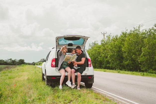 Szczęśliwa urocza rodzina taty, mamy i syna podróżuje samochodem i zatrzymała się na poboczu drogi, aby zobaczyć mapę.