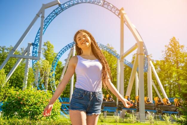 Szczęśliwa uśmiech dziewczyna stoi w parku rozrywki w słonecznym dniu. modny portret.