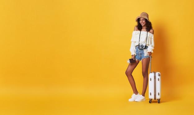 Szczęśliwa uśmiechnięta afrykańska kobieta ubierał w lecie odziewa z bagażem cieszy się ich wakacje wjazd w kolorze żółtym z kopii przestrzenią.
