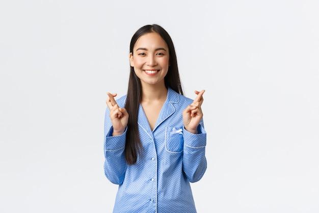 Szczęśliwa uśmiechnięta azjatka w niebieskiej piżamie mająca wiarę w spełnienie marzeń, krzyżujące palce powodzenia, życzące sobie jako oczekujące na ważne rezultaty, stojąca na białym tle optymistycznie.