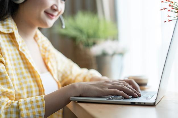 Szczęśliwa uśmiechnięta azjatycka kobieta call center i operator noszący zestawy słuchawkowe pracujące na komputerze i rozmawiające z klientem z jej umysłem obsługi