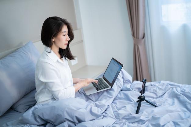 Szczęśliwa uśmiechnięta azjatycka młoda kobieta z laptopem i telefonem komórkowym o rozmowie wideo w sypialni
