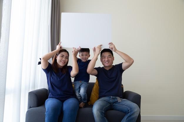 Szczęśliwa uśmiechnięta azjatycka rodzina trzymająca pusty duży biały plakat i siedząca na kanapie w salonie